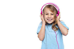 Excited girl enjoying music through headphones